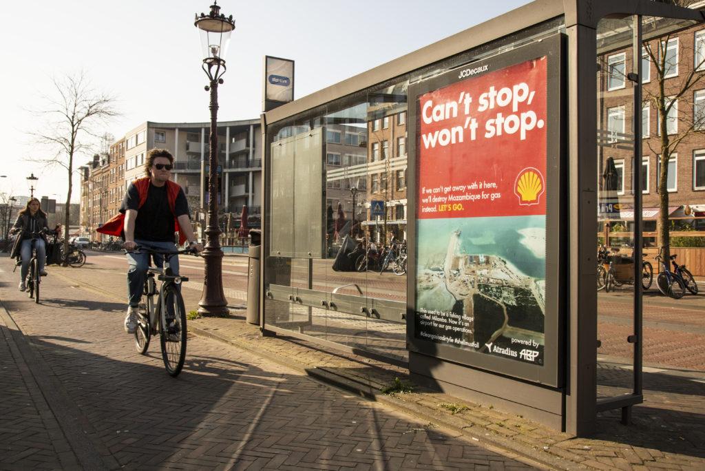 Een man fietst langs een bushokje waar een poster hangt met boven rood en onder een birds eye view van een vliegveld. Op de poster staat 'Can't stop, won't stop